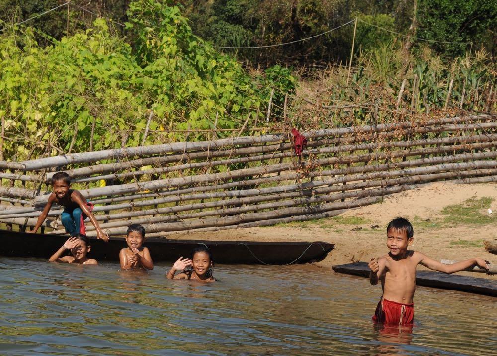 Kinderen spelen in de Nam Tha rivier in het noorden van Laos.